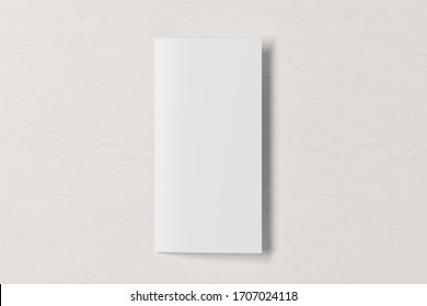 Blank square leaflet on white wooden background. Bi-fold or half-fold closed brochure isolated with clipping path. View directly above. 3d illustration