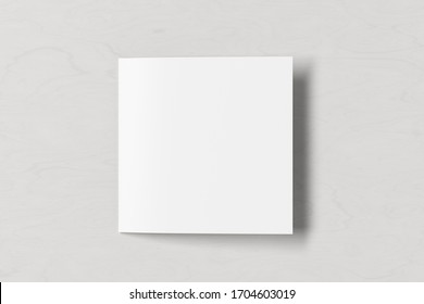 Blank square pages leaflet on white wooden background. Bi-fold or half-fold closed brochure isolated with clipping path. View directly above. 3d illustration