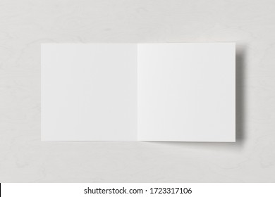 Blank square pages leaflet on white wooden background. Bi-fold or half-fold opened brochure isolated with clipping path. View directly above. 3d illustration