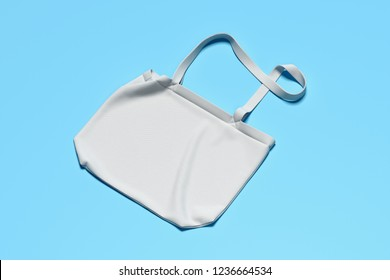 Blank white bag on light blue background, business template for branding identity. Shopping concept. 3D rendering.