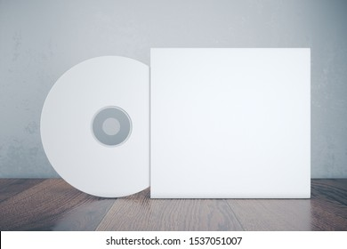 Blank white compact disk with cover on wooden table. Mock up, 3D Rendering