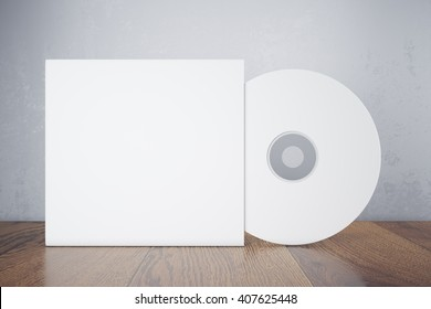 Blank white compact disk with cover on wooden table and concrete wall background. Mock up, 3D Rendering