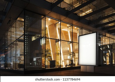 Blank white illuminated banner at night time next to commercial or business center. 3d rendering