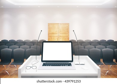 Blank white laptop placed on speaker's stand in conference hall interior with rows of seats and wooden door. Mock up, 3D Rendering