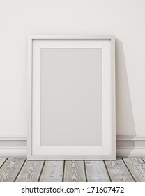 blank white picture frame on the white wall and the wooden floor, background