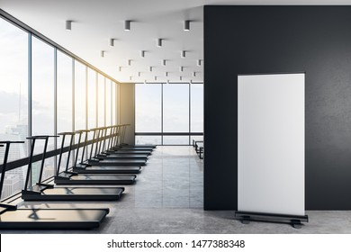 Blank white poster on concrete floor in modern gym with black treadmills, big light windows and city view. 3D Rendering