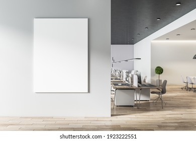Blank white poster on light grey wall in modern open space office with light furniture and wooden floor. Mock up. 3D rendering