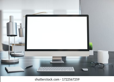 Blank white screen of computer monitor and coffee mug on table in office. 3D Rendering