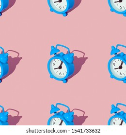 Blue alarm clock on a green background. Set. Seamless texture pattern. Long harsh shadow from the summer sunshine.