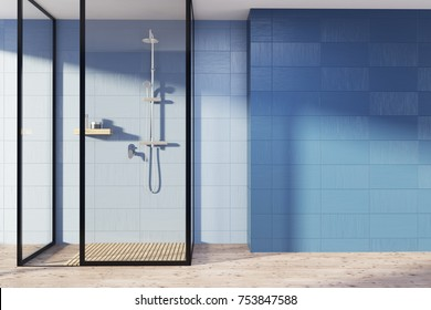 Blue bathroom interior with a wooden floor, a shower stall with glass walls and an empty wall fragment. 3d rendering mock up