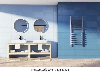 Blue bathroom interior with a wooden floor, a double sink with two round mirrors and a towel rack. 3d rendering