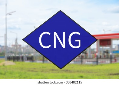 Blue diamond symbol with text CNG. Out-of-focus background - Fueling station.