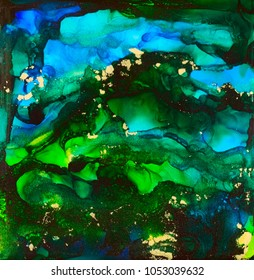 Blue and green shades and gold dust in alcohol inks.