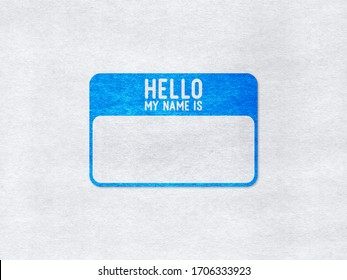 """Blue name tag """"Hello my name is"""" on a paper background"""