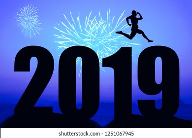 Blue night fireworks with new year 2019 silhouette and jumping man as symbol for success and vitality
