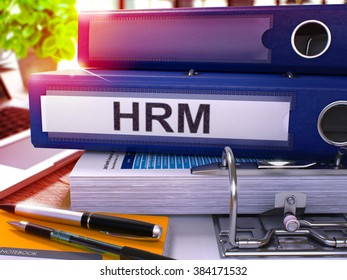 Blue Office Folder with Inscription HRM - Human Resources Management - on Office Desktop with Office Supplies and Modern Laptop. HRM Business Concept on Blurred Background. HRM - Toned Image. 3D.