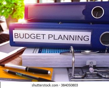 Blue Ring Binder with Inscription Budget Planning on Background of Working Table with Office Supplies and Laptop. Budget Planning Business Concept on Blurred Background. 3D Render.