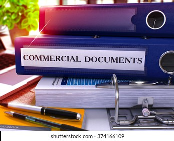 Blue Ring Binder with Inscription Commercial Documents on Background of Working Table with Office Supplies and Laptop. Commercial Documents Business Concept on Blurred Background. 3D Render.