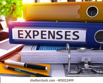 Blue Ring Binder with Inscription Expenses on Background of Working Table with Office Supplies and Laptop. Expenses - Toned Illustration. Expenses Business Concept on Blurred Background. 3D Render.