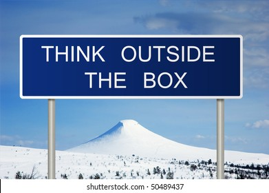 A blue road sign with white text saying think outside the box