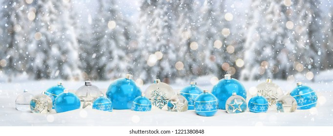 Blue and silver christmas baubles on snowy background 3D rendering