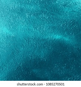 Blue teal sea water texture view from above light movement . Sea view- foam and ripples on sea water surface.
