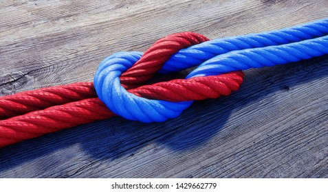 Blue und red reef knot or square knot on dark wood - 3D illustration