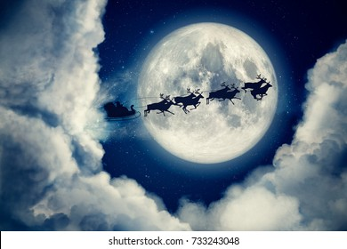 Blue xmas eve night with moon and clouds with Santa Claus sleight and reindeer silhouette flying to bring gifts and presents with text space to place logo or copy. Christmas present greeting post card