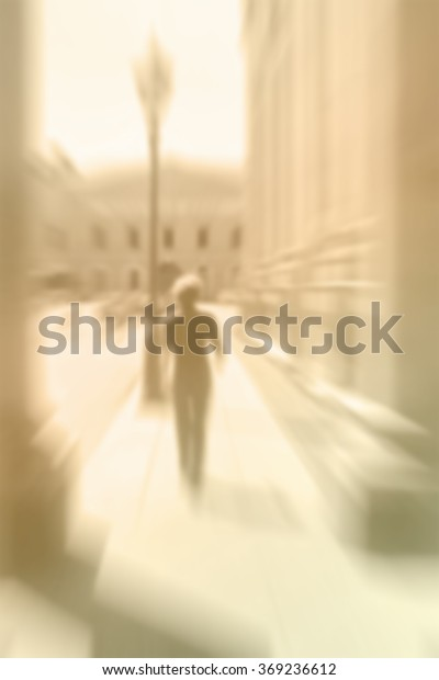 Blurred image of a moving man walking along classy old town street. Vintage aged look.