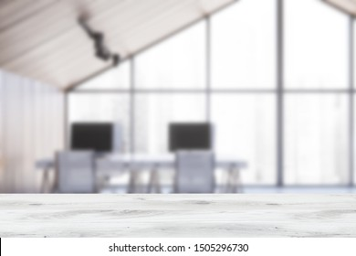 Blurred interior of attic open space office with wooden walls, large window and stylish white computer desks with metal chairs. Table for your product in foreground. 3d rendering