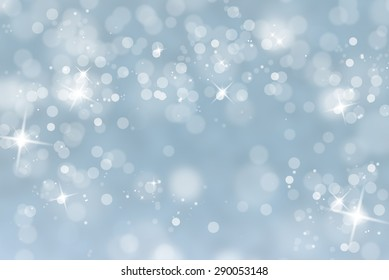 Blurry abstract bokeh lights on light blue background with sparkle.