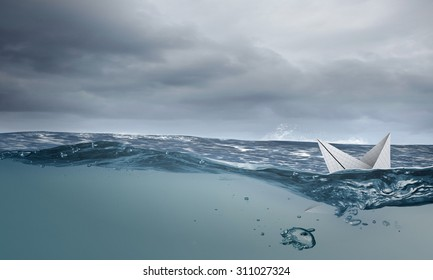 Boat made of paper sinking in blue water surface