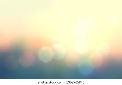 Bokeh pattern on summer forest blurred background. Yellow orange blue green gradient. Bright lights of dawn sky. Abstract pattern. Natural illustration.