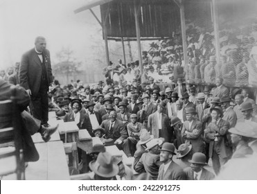 Booker T. Washington addressing a laughing crowd of African American men in Lakeland, Tennessee, during his campaign promoting African American education. Ca. 1900.