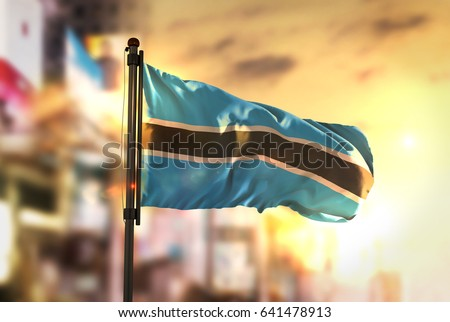 Botswana Flag Against City Blurred Background At Sunrise Backlight 3D Rendering
