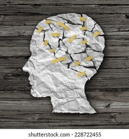 Brain disease therapy and mental health treatment concept as a sheet of torn crumpled white paper taped together as a human face on wood as a symbol for neurology surgery  or psychological help.