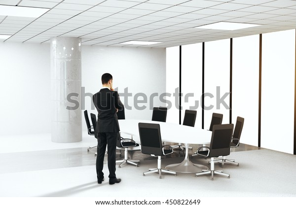 Brainstorming businessman in boardroom interior with round table, chairs and concrete column. 3D Rendering