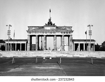 The Brandenburg Gate in East Berlin behind the Berlin Wall A sign in German warns of the border between East and West Berlin Aug.