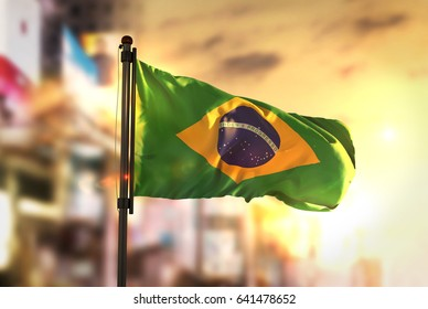 Brazil Flag Against City Blurred Background At Sunrise Backlight 3D Rendering