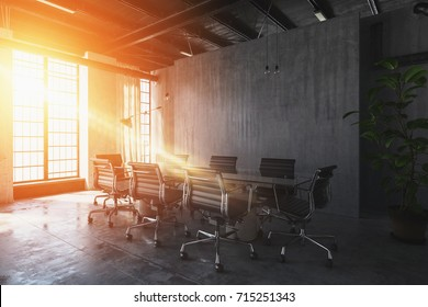 Bright, warm sunset light streaming through windows into an industrial style office with table and chairs. 3d Rendering.