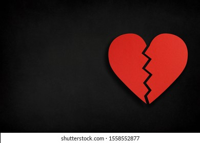Broken heart shape made from cut paper with copy space on black background