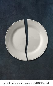 Broken white plate isolated on dark gray slate stone background