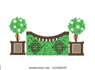 Brown gated cross-country jump with boxwood brush, decorative trellis designs, and cream flowered topiary plants in panel planters as the jump wings.