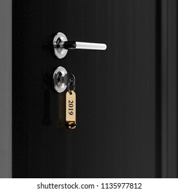 Brown hotel room door with key in the lock with golden lable number 2019 new year concept