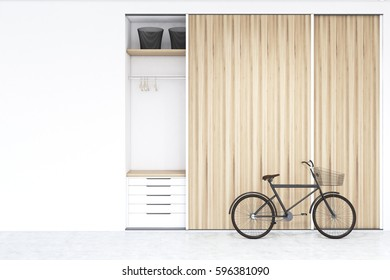Built in wooden wadrobe in a room with hangers and boxes, a set of drawers is in the lower part. There is a bike standing beside it. 3d rendering, mock up