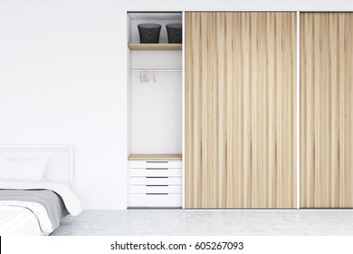 Built in wooden wadrobe in a room with hangers and boxes, a set of drawers is in the lower part. There is a double bed to the left. 3d rendering, mock up