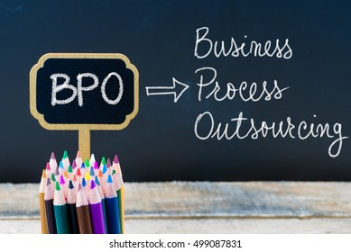 Business Acronym BPO Business Process Outsourcing written with chalk on wooden mini blackboard labels and chalkboard background.