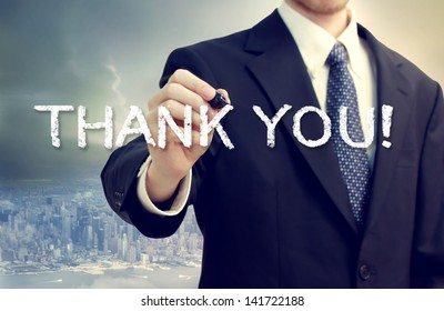 Business Man Drawing THANK YOU On A Big City Background