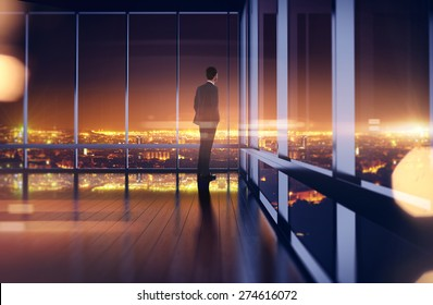 Business man in suit looking at the night city. 3d rendering