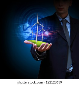 Business man and a windmills as a symbol of green energy